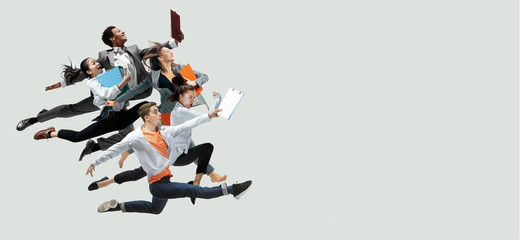 Happy office workers jumping and dancing in casual clothes or suit with folders isolated on studio background. Business, start-up, working open-space, motion and action concept. Creative collage. Wall mural
