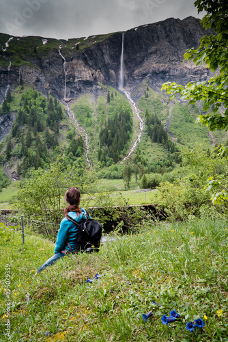Wall mural woman hiker looks at high picturesque waterfalls in lush green forest and mountain landscape