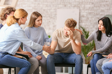 Fotomurales - People calming depressed man at group therapy session