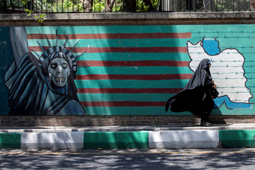 A woman walks past the mural showing U.S. flag with barbed wire and the Statue Of Liberty with skull face in Tehran