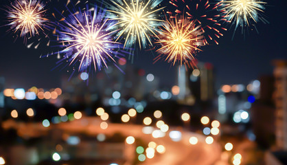abstract group of  colorful multi fireworks explosion on blur night cityscape town background with text for fourth of july celebrate concept