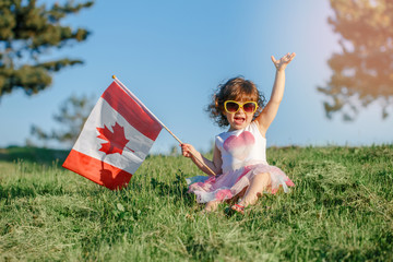 Papiers peints Canada Portrait of adorable cute little Caucasian baby toddler girl sitting on green grass in park outside and holding waving large Canadian flag. Kid child citizen celebrating Canada Day on 1st of July.