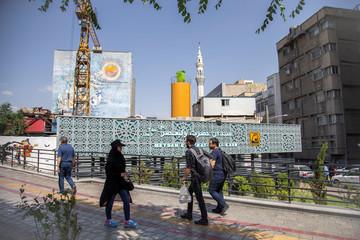 People walk in front of Meydan E Hazrat-E Vali-E Asr metro station in Tehran