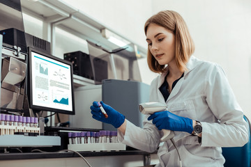 Smart blonde woman holding a test tube with blood
