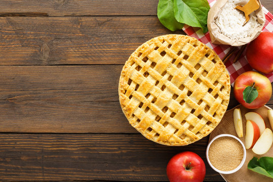 Apple pie with lattice top and ingredients on wooden table.