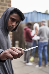 Teenage Boy In Urban Gang Pointing Knife Towards Camera