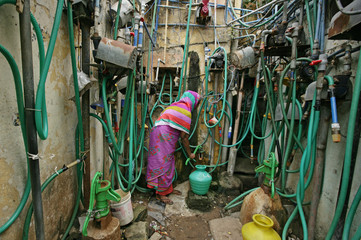 A woman uses a hand pump to fill up a container with drinking water in Chennai