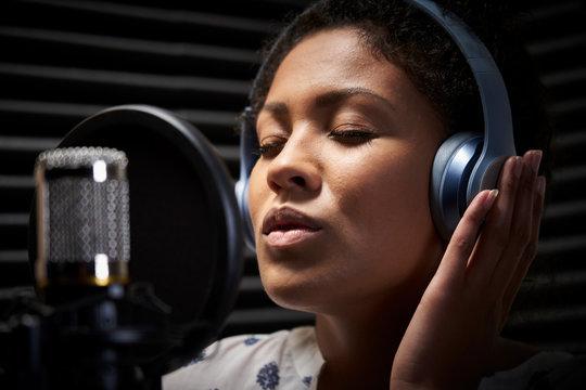 Female Vocalist Wearing Headphones Singing Into Microphone In Recording Studio