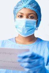 Studio Portrait Of Female Surgeon Wearing Gown And Mask Holding Medical Print Out