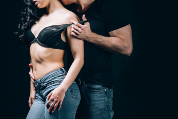 cropped view of couple kissing and undressing isolated on black