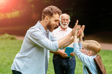 Image of a modern beard father giving a hi-five his little son with grandfather on background in the park. Dad and granddad meets their son from elementary school. the end of the school day concept