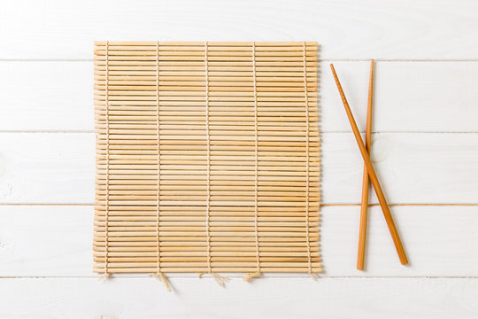two sushi chopsticks with empty bamboo mat or wood plate on wooden Background Top view with copy stace