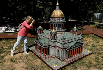 """A woman takes a picture of a model of the Saint Isaac's Cathedral (Isaakievskiy Sobor) is seen at the """"RussiainMiniature"""" exhibition in Moscow"""