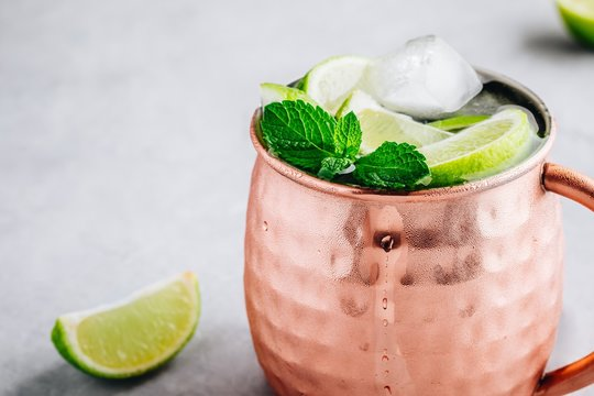 Moscow mule ice cold cocktail in copper cup with lime and and mint on gray stone background