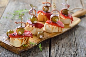 Spanische Tapas: Gegrilltes Baguette mit geröstetem und eingelegtem Paprika, gefüllten Oliven und Sardellenfilets - Spanish snack:Grilled bread with roasted peppers, stuffed olives and anchovy fillets