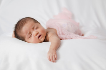 Adorable asian newborn baby in pink wrap sleeping on white blanket background.