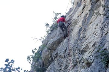Mann klettert an der Felswand