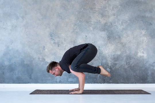 Sporty young man working out, doing handstand yoga asana, Crow Pose or Bakasana