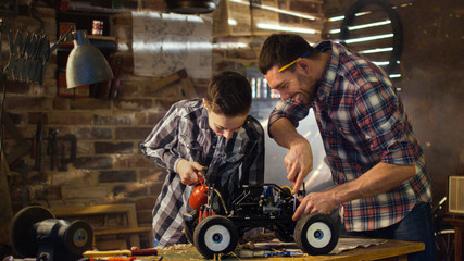 Father and son are working on a radio control toy car in a garage at home.