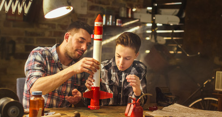 Father and son are modeling a toy rocket in a garage at home.