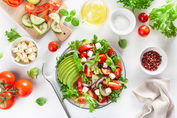 greek style avocado tomato salad with feta cheese, olives, cucumber, onion, lettuce