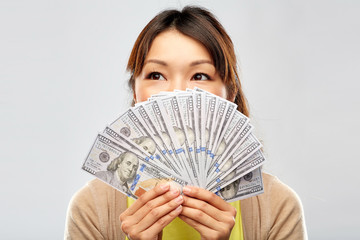 people, ethnicity and portrait concept - happy asian young woman holding hundreds of dollar money...