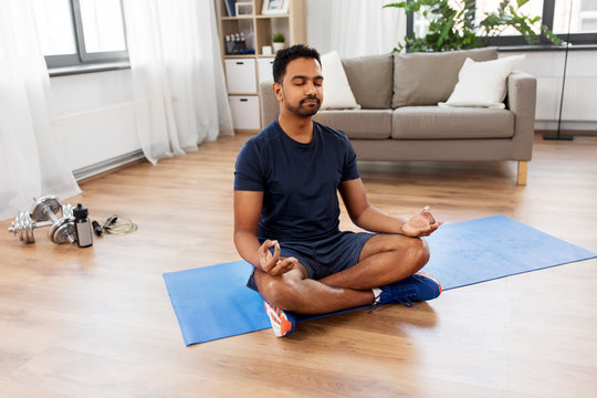 fitness, meditation and healthy lifestyle concept - indian man meditating in lotus pose on exercise mat at home