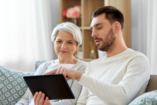 family, generation and technology concept - happy smiling senior mother and adult son with tablet computer at home