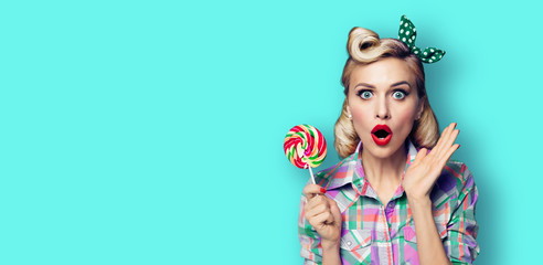 Photo of beautiful very surprised woman with lollipop, in pinup style, over blue green color background