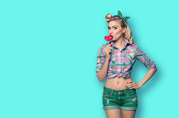 Photo of young woman eating heart shape lollipop, dressed in pinup style, over green color background