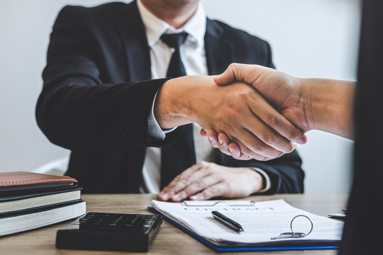 Broker and client shaking hands after signing contract approved form