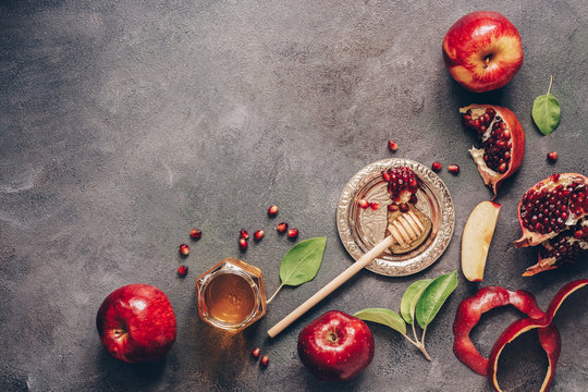 Apples, pomegranate and honey on a dark rustic background. Traditional Jewish food. New Year - Rosh Hashanah. Top view, copy space, flat lay.