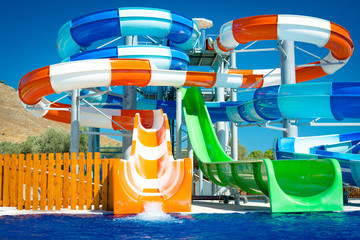 colorful open-air water slides, Detail of the orange and green slides, front view