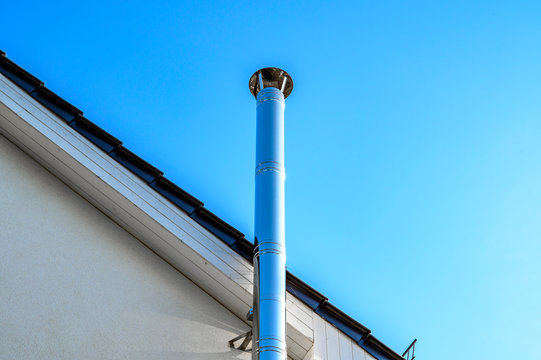 Stainless steel chimney and parts of a roof in front of a bright blue sky.