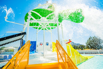 Children's water playgrounds and flip-flops with flowing, falling and splashing water. Moment pouring the bucket with water. In the background azure sky. The sun in the shot.