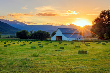 Rural sunset with hay bales and an old barn in the countryside, Utah, USA. Wall mural
