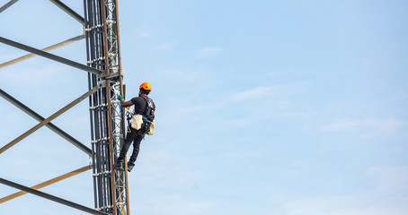 Telecom maintenance. Worker climber on tower against blue sky background Fotomurales