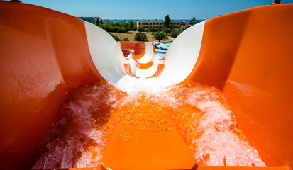 start position on water slide, orange tobogan, , in the background hotel and sea