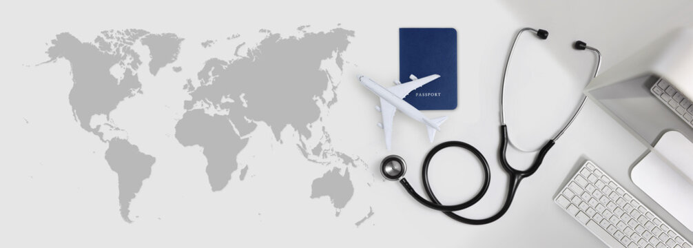 international medical travel insurance concept, stethoscope, passport, computer and airplane on desk office banner with global map
