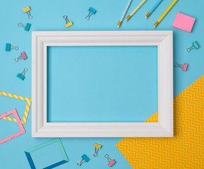 Flat lay empty frame and office supplies on blue pastel background