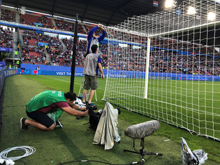 Photographers set remote cameras behind the goal before the Japan-Holland match during the Women's World Cup soccer tournament in Rennes