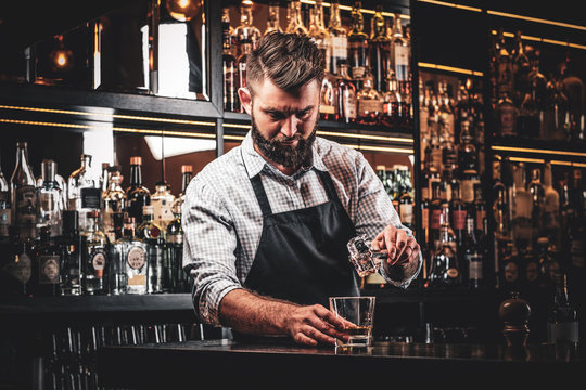 Diligent serious barman is preparing alcoholic beverege for customer.