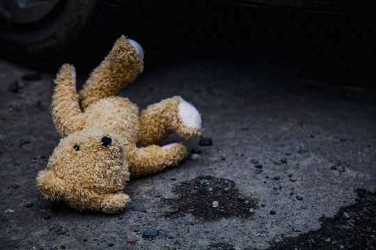 Concept: lost childhood, loneliness, pain and depression. Teddy bear lying down outdoors.