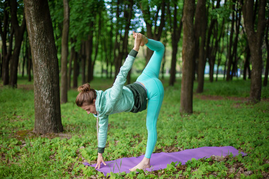 Thin beautiful sporty girl standing in Half Moon pose, Ardha Chandrasana exercise in a summer park. Green lush forest on the background. Woman doing exercises on a yoga mat