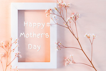 White wooden frame on a coral textured background with small flowers and the inscription Happy Mother's Day - greeting card