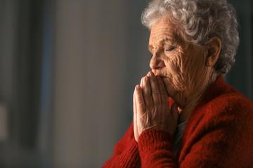 Senior woman praying to God at night Wall mural