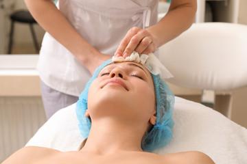 Fototapeta Beautiful woman undergoing facial treatment in beauty salon