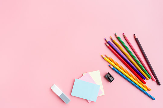 School supplies stationery, colour pencils, paints, paper on pink background, back to school concept with free copy space for text, modern elementary education. Kids desk, flat lay, top view, mockup.