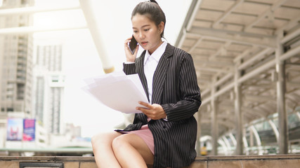 Wall Mural - Portrait of young business woman reading newspaper outdoors