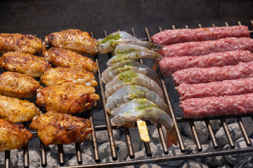 Mixed assortment of marinated meat, chicken, and prawns grilling on hot coals on a BBQ